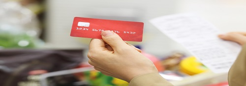 Close up of hand holding a red credit card