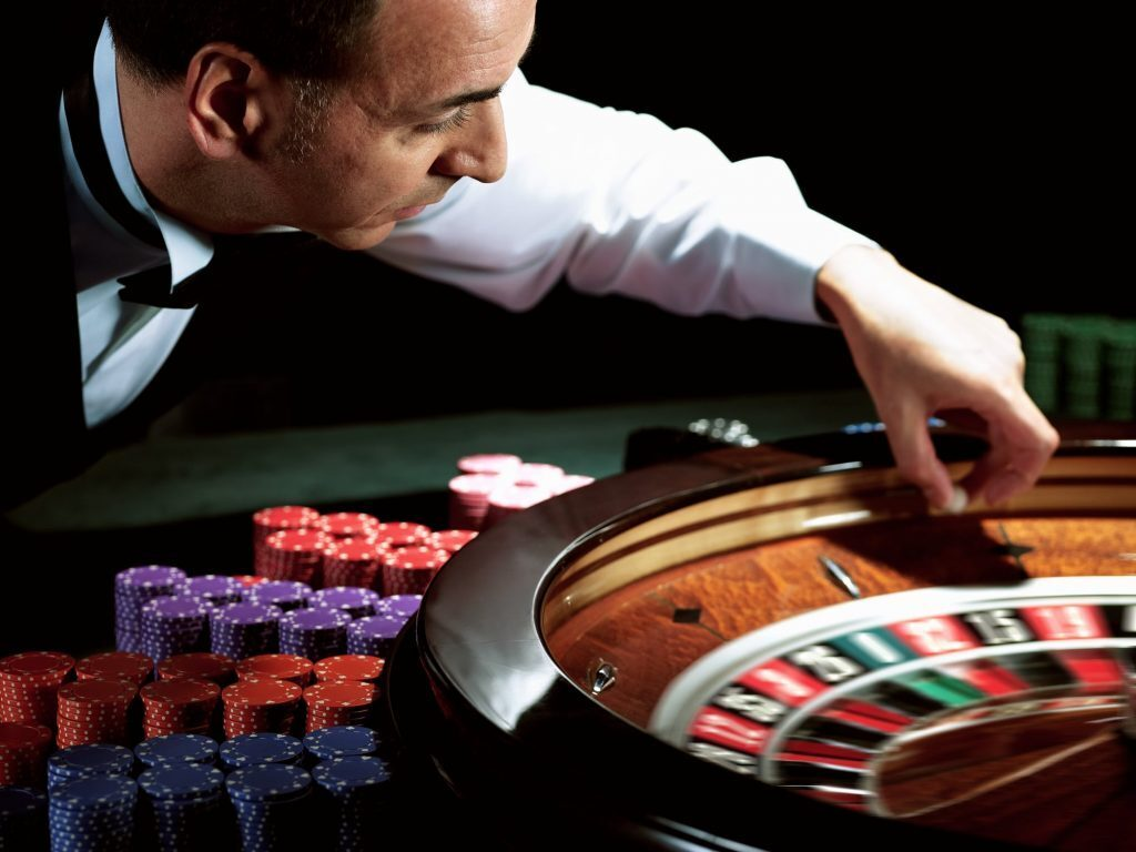 Dealer placing the ball into a roulette wheel.