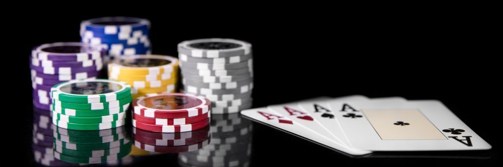 Poker chips sitting next to four aces(playing cards).