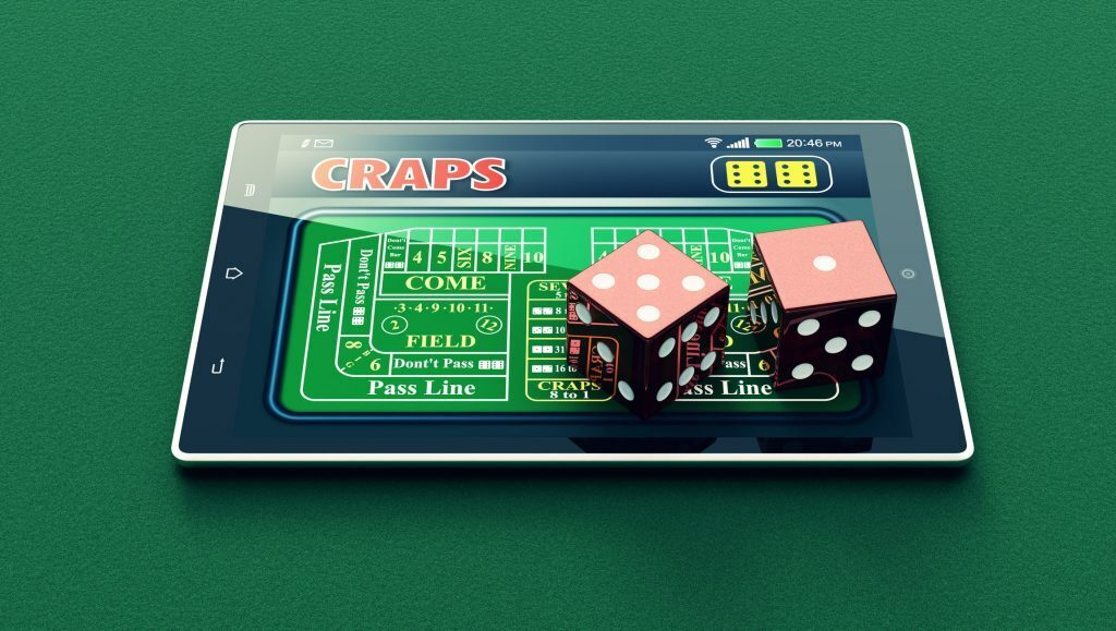 Dice sitting on tablet that is playing digital craps.