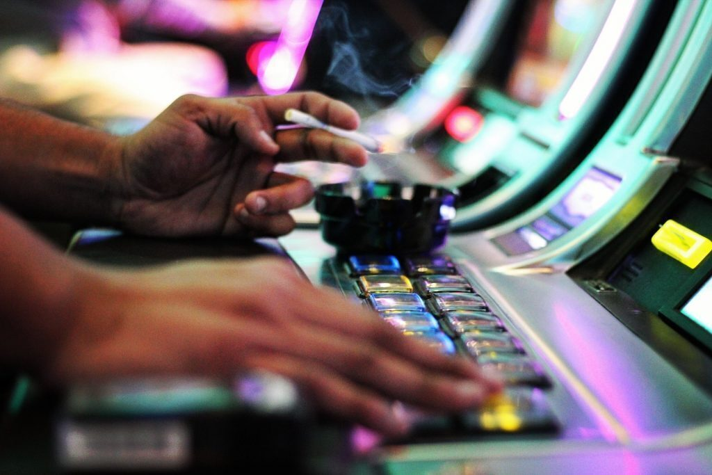 Close up of persons' hands playing slots